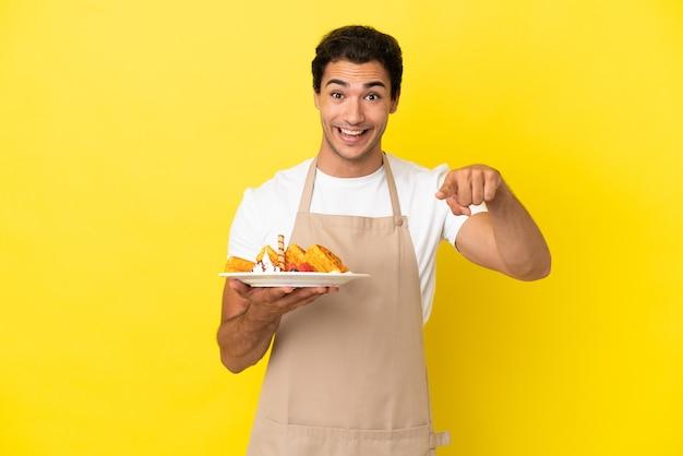 Официант ресторана, держащий вафли на изолированном желтом фоне, удивлен и показывает вперед
