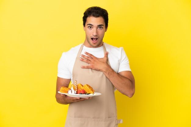 孤立した黄色の背景の上にワッフルを持っているレストランのウェイターは、右を見ながら驚いてショックを受けました