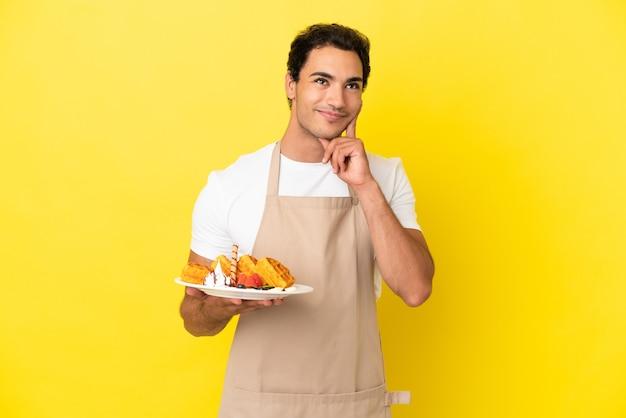Официант ресторана держит вафли на изолированном желтом фоне, думая об идее, глядя вверх