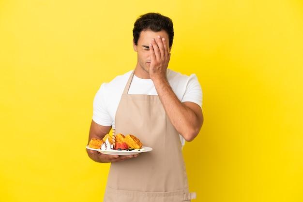 Официант ресторана держит вафли на изолированном желтом фоне с усталым и больным выражением лица