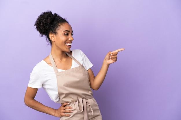 Официант ресторана латинская женщина изолирована на фиолетовом фоне, указывая пальцем в сторону и представляет продукт