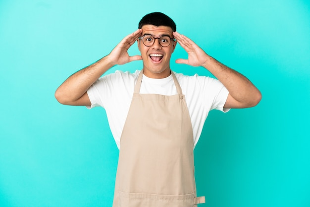 Restaurant waiter man over isolated blue wall with surprise expression