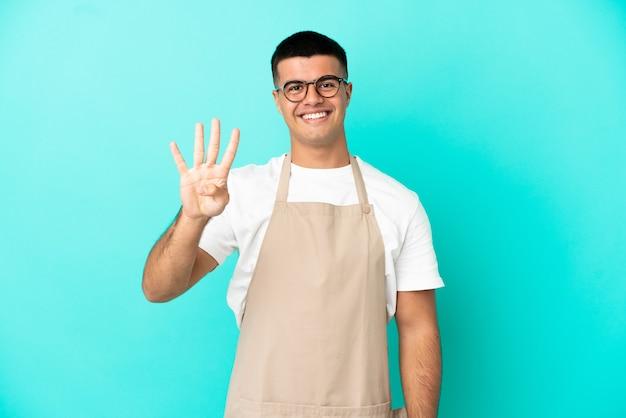 Ресторан официант человек на изолированном синем фоне счастлив и считает четыре пальцами
