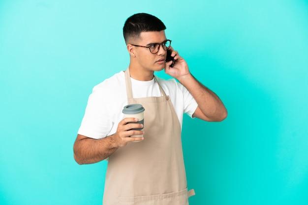 테이크 아웃 커피와 모바일을 들고 고립 된 파란색 배경 위에 레스토랑 웨이터 남자