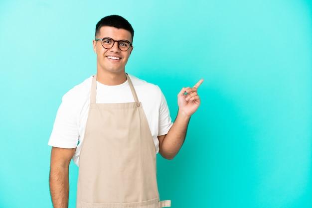 Ресторан официант человек на изолированном синем фоне, указывая пальцем в сторону