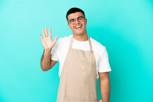 Ресторан официант человек на изолированном синем фоне салютует рукой с счастливым выражением лица
