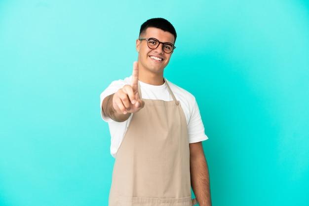 Ресторан официант мужчина на изолированном синем фоне показывает и поднимает палец