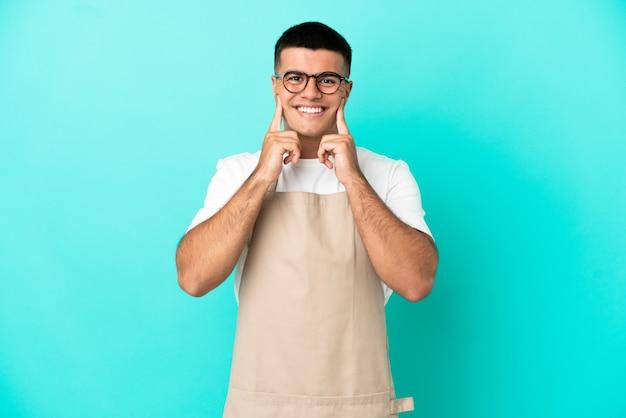 Ресторан официант мужчина на изолированном синем фоне улыбается со счастливым и приятным выражением лица