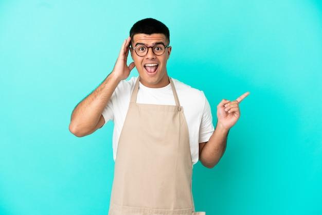 Ресторан официант мужчина на изолированном синем фоне удивлен и указывает пальцем в сторону