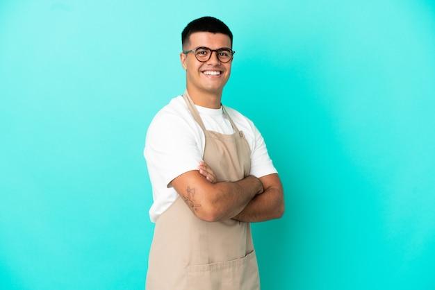 Ресторан официант мужчина на изолированном синем фоне со скрещенными руками и с нетерпением ждет