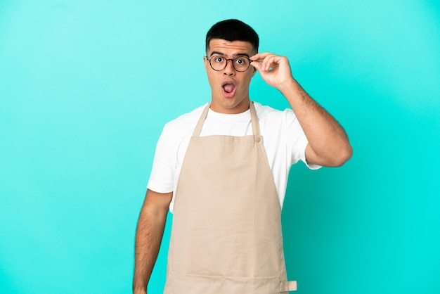 Ресторан официант мужчина на изолированном синем фоне в очках и удивлен