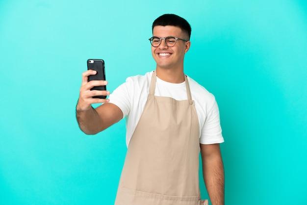 Ресторан официант мужчина над изолированной синей стеной, делая селфи