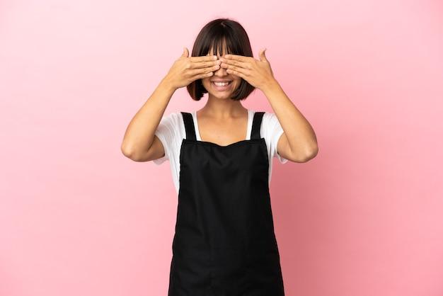 Официант ресторана на изолированном розовом фоне, закрывая глаза руками и улыбаясь Premium Фотографии