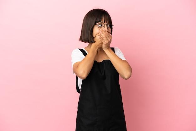 Официант ресторана на изолированном розовом фоне прикрывает рот и смотрит в сторону