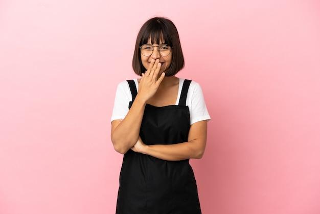 孤立したピンクの背景の上のレストランのウェイター幸せと笑顔の手で口を覆う
