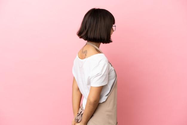 Официант ресторана на изолированном розовом фоне в заднем положении и оглядываясь назад