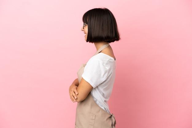 Официант ресторана на изолированном розовом фоне в боковом положении