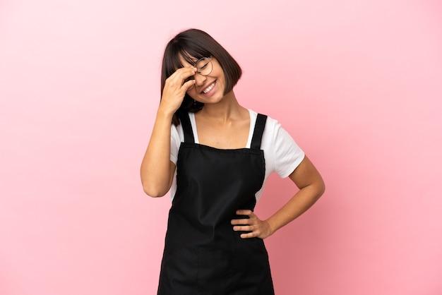 Официант ресторана на изолированном розовом фоне смеется