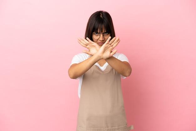 Официант ресторана на изолированном розовом фоне делает жест рукой, чтобы остановить выступление