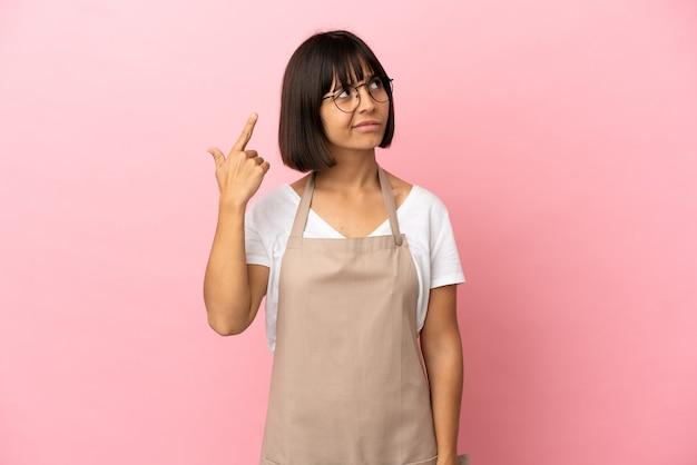 Официант ресторана на изолированном розовом фоне делает жест безумия, положив палец на голову