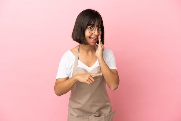 Официант ресторана на изолированном розовом фоне, указывая в сторону, чтобы представить продукт, и что-то шепчет