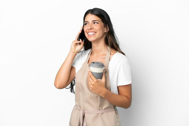 持ち帰り用のコーヒーと携帯電話を保持している孤立した白い背景の上のレストランのウェイター