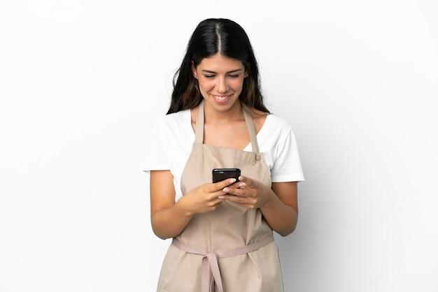 Официант ресторана на изолированном белом фоне, отправив сообщение с мобильного телефона