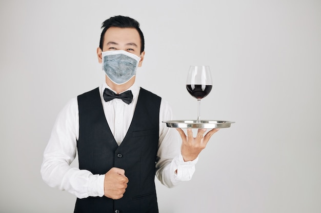 Официант ресторана, подающий вино