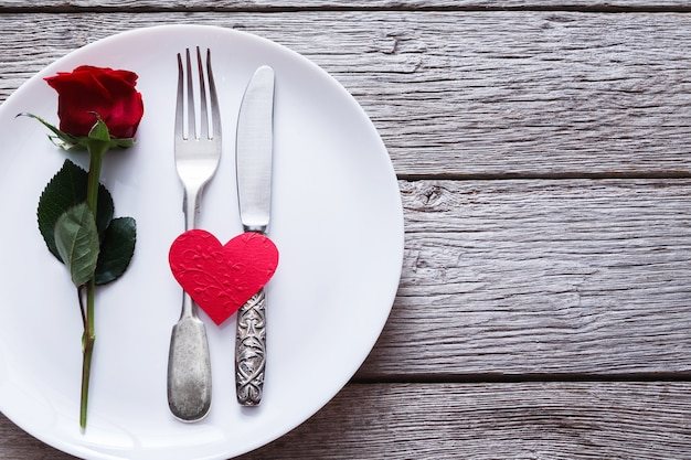 Restaurant wooden table with heart and rose with cutlery on plate