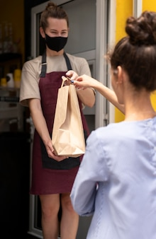 Restaurant worker handing the order to a client