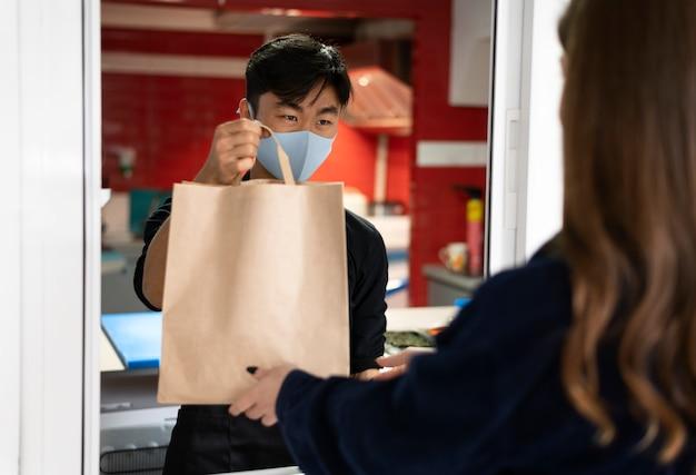 Работник ресторана передает заказ клиенту