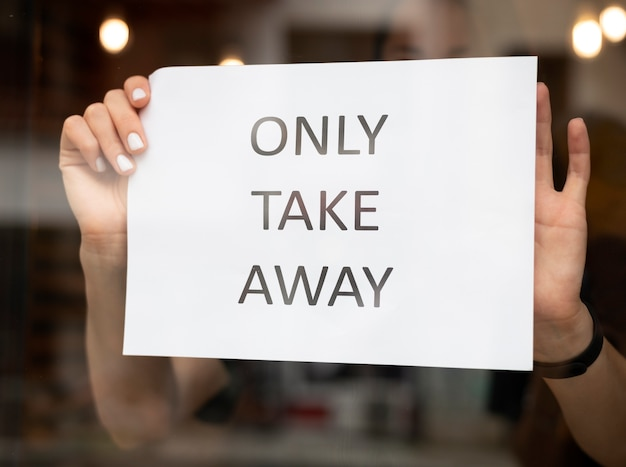 Restaurant worker putting a takeaway sign in front o the restaurant