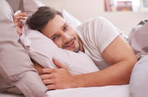 Отдохнувший мужчина, лежа в постели утром