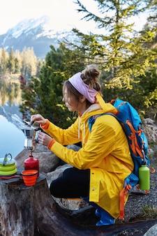편안한 여성 여행자는 캠핑 스토브에서 커피를 만들고, 그루터기 근처에서 포즈를 취하고 방황 후 휴식을 취합니다.