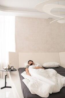 큰 침대에서 하얀 시트 아래에서 자고 있는 편안한 남자