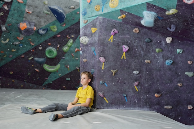 Restful schoolboy in activewear sitting on mat against climbing wall after training while enjoying break