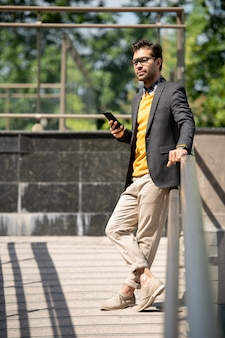 Спокойный молодой бизнесмен в элегантной повседневной одежде наслаждается летним днем в городе во время прокрутки в смартфоне