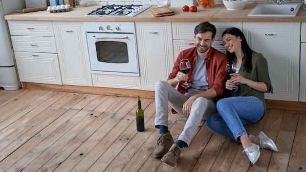 の床に座っている若い幸せなロマンチックなカップルの妻と夫を料理した後に休む