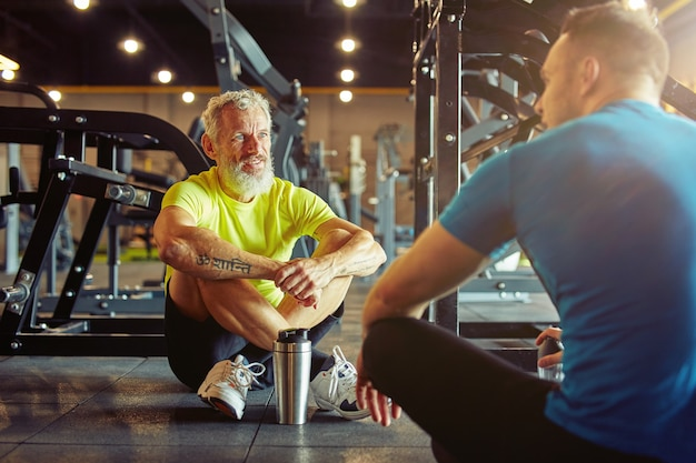 Resting after training athletic middle aged man discussing something with fitness instructor or