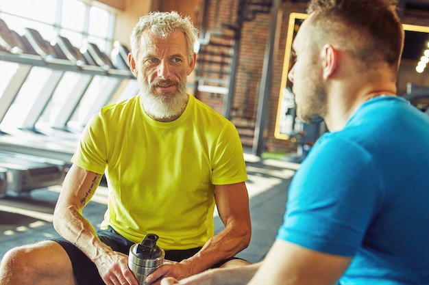Resting after workout focused middle aged man in sportswear holding bottle of water and talking