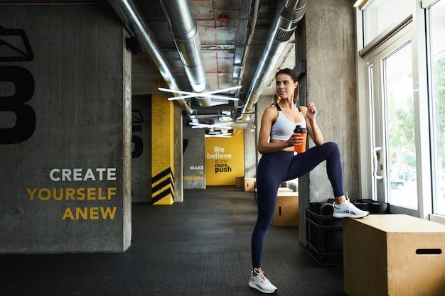 운동복을 들고 병을 들고 있는 젊고 아름다운 피트니스 여성의 전체 길이 운동 후 휴식