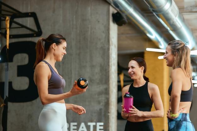 운동 후 휴식. 운동복을 입은 3명의 아름다운 피트니스 여성 그룹은 체육관에서 휴식을 취하는 동안 이야기하고 웃고 있습니다. 스포츠, 웰빙 및 건강한 라이프 스타일