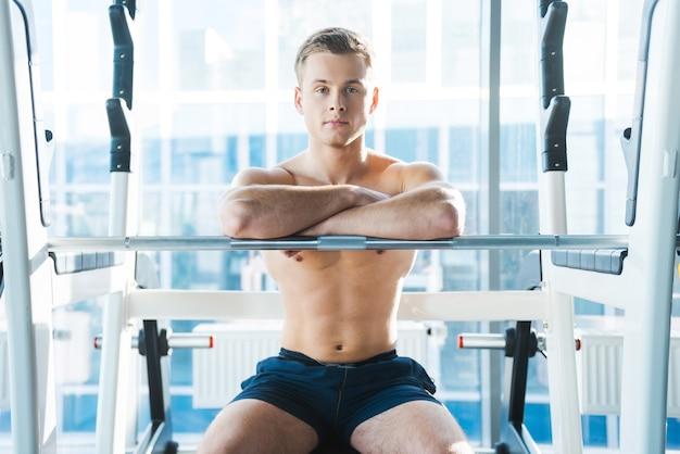 ワークアウトセッション後に休憩します。ベンチプレスに座って腕を組んでカメラを見ている自信のある若い筋肉の男
