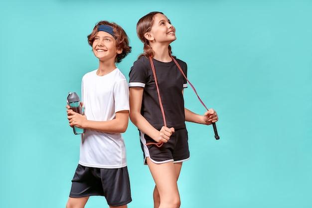 운동 후 휴식을 취하는 두 십대 소년과 소녀는 줄넘기와 물병을 찾고 있습니다.