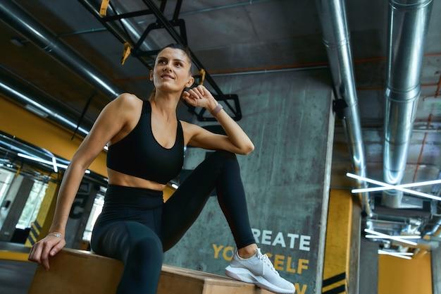 トレーニング後に休憩。ジムで木製のcrossfitジャンプボックスに座って脇を見ているスポーツウェアの若い美しい運動少女。スポーツの人々、トレーニング、健康的なライフスタイルの概念