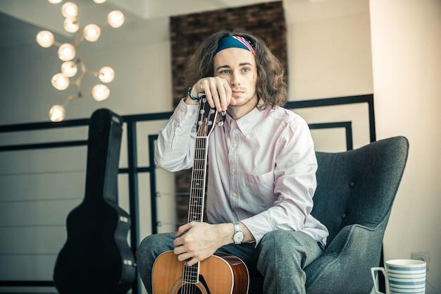 Отдыхаю дома. привлекательный молодой человек с голубыми глазами, грустно глядя в окно, неся акустическую гитару