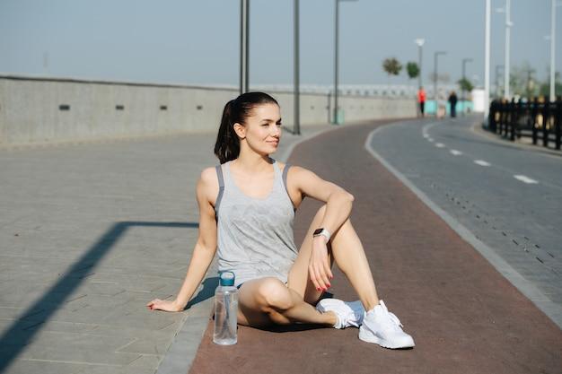쉬고 있는 운동 여성이 야외 트랙에 앉아 태양 광선을 즐기고 있습니다. 맑고 푸른 하늘 아래 화창한 날. 그녀는 흰색 민소매 셔츠와 미니 반바지를 입고 있습니다.