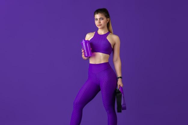 Отдыхает. красивая молодая спортсменка, практикующая в студии, монохромный фиолетовый портрет.