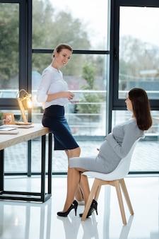 Отдыхаем во время обеда. полноценные позитивные коллеги, выражающие волнение во время перерыва
