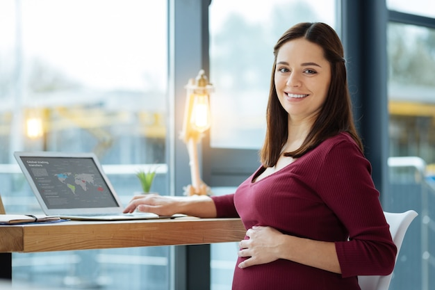 Resting at home. close up of smiling pregnant woman using a laptop while touching her stomach and expressing optimism